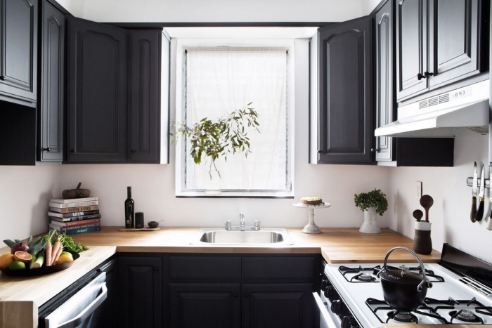 dark u-shaped kitchen with a wooden countertop