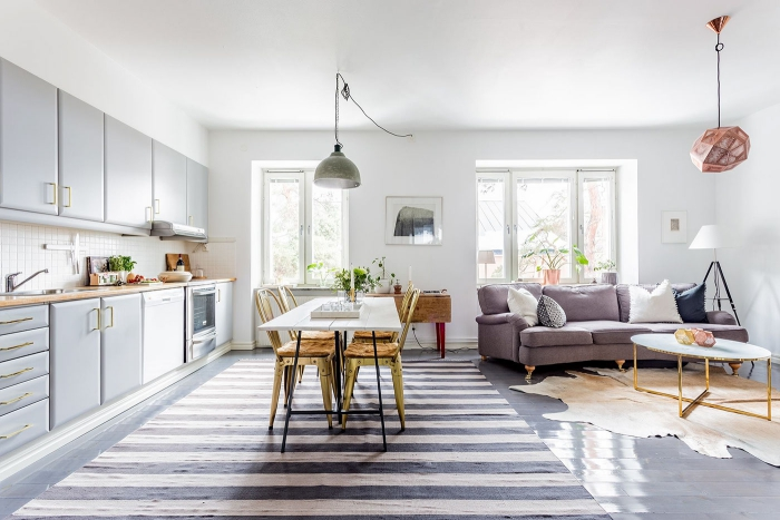 Grey and white airy light living area with kitchen dining table and sofa