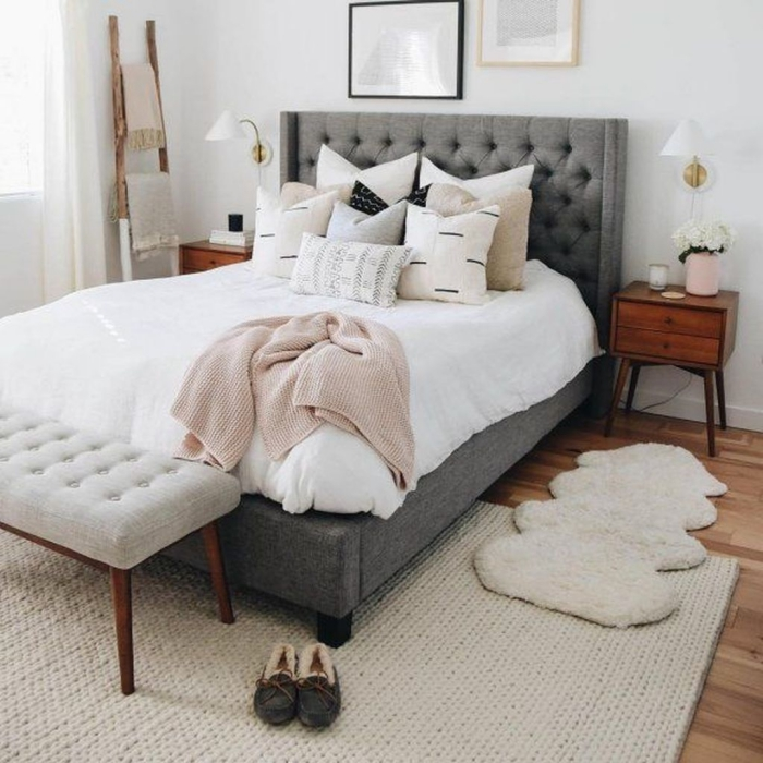 comfortable big grey bed in a light bedroom with warm rug