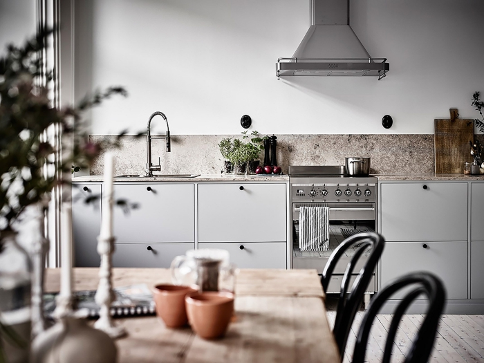 Small white one-unit kitchen with black chairs and metallic surfaces