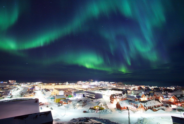 Northern lights over Greenland night sky with aurora over snowy town landscape