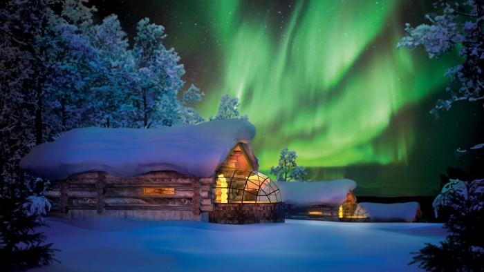 Northern lights in the winter night sky wooden houses with glass roof covered terrace