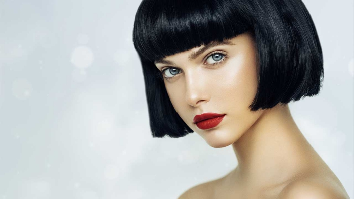 woman with pale skin black hair blue eyes and red lips on a light background