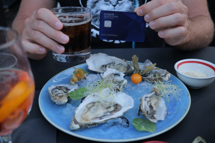 Person showing Chase Sapphire Preferred card on a table oyster plate drink lunch