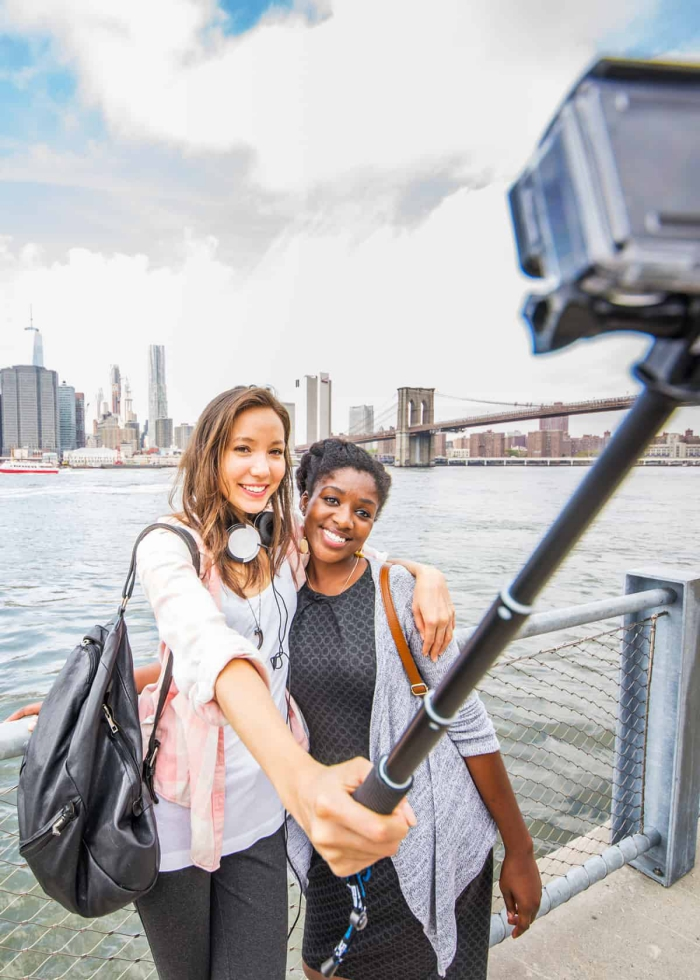 two girls taking a picture with a selfie stick on a river