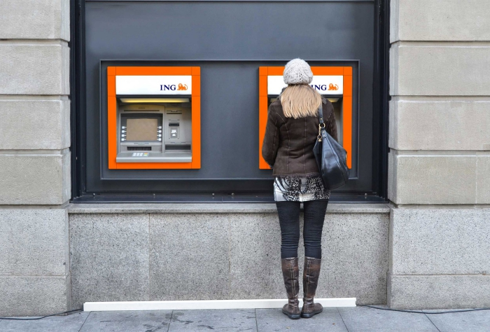 Woman with a hat in front of two ING ATMS money withdrawal