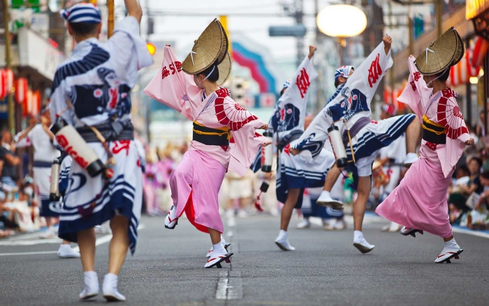 Japanese girls in pink and white dancing at one of their big festivals