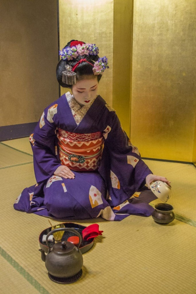 Japanese girl in traditional clothes doing Tea ceremony