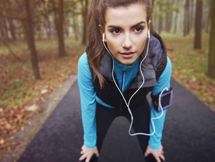 Woman with brown eyes jogging in a park with headphones and phone