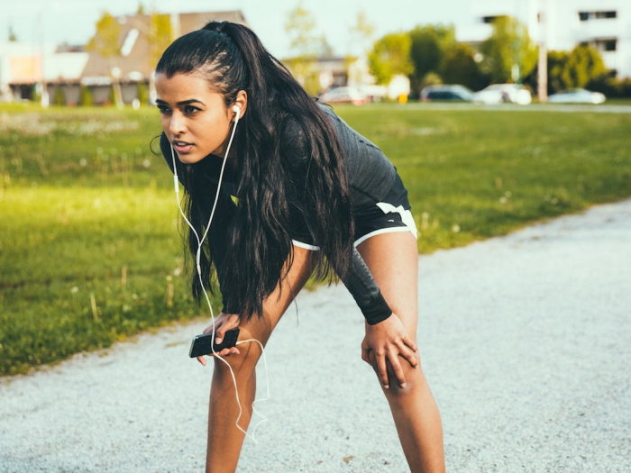 Woman jogging in black shorts and headphones and phone