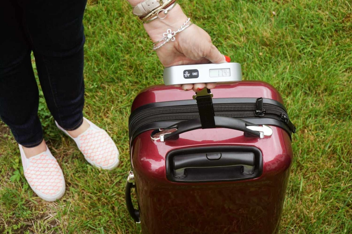 woman with a luggage scale weighing a red suitcase on a lawn