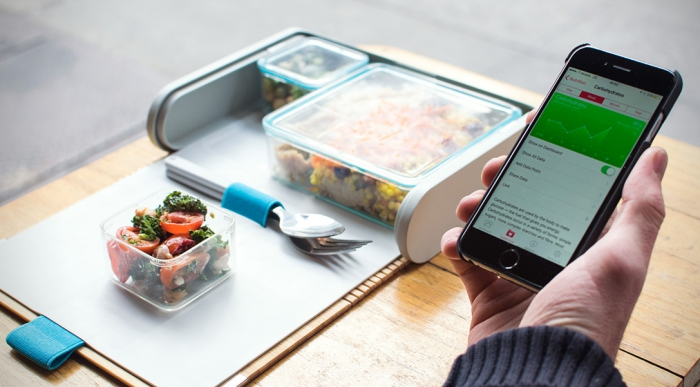 Modern lunchbox for adults man with a phone eating lunch from a lunch kit