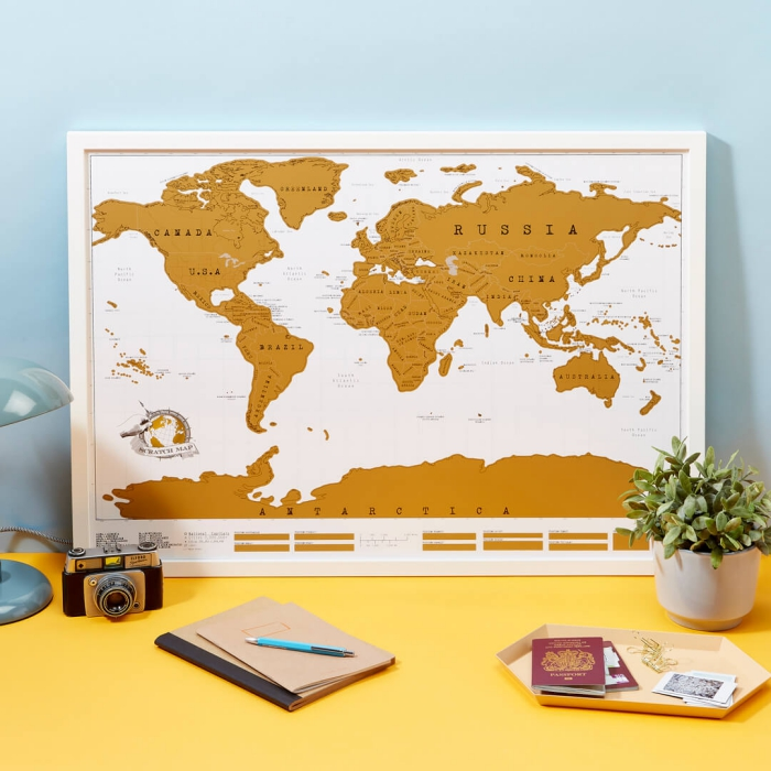 unique travel gifts ideas scratch map on a desk with photo camera passports notebooks