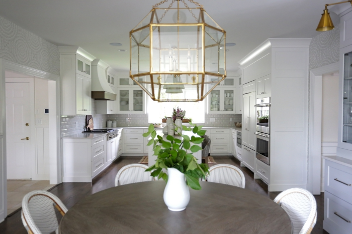 sophisticated white kitchen and dining area with metal and glass lighting fixture