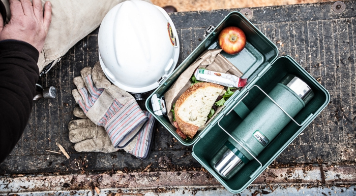 Stainless steel lunch box with sandwich and apple worker at work