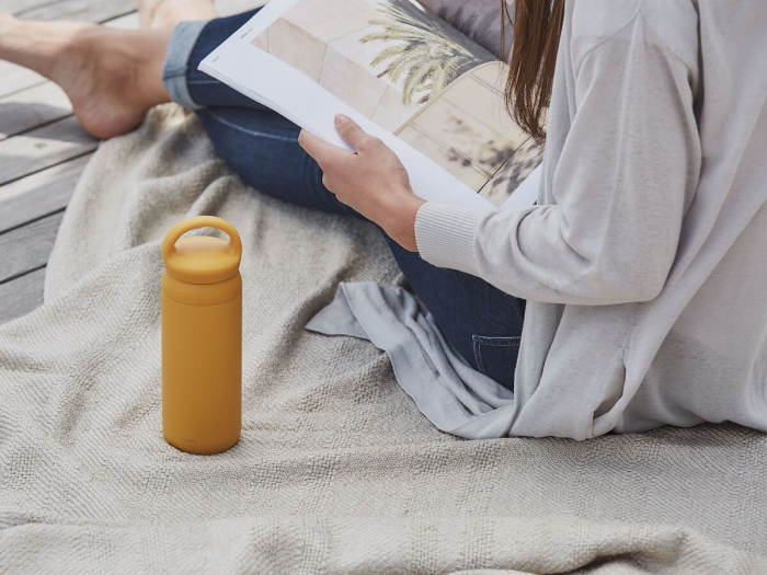 travel gift ideas woman reading a magazine with a yellow thermos bottle