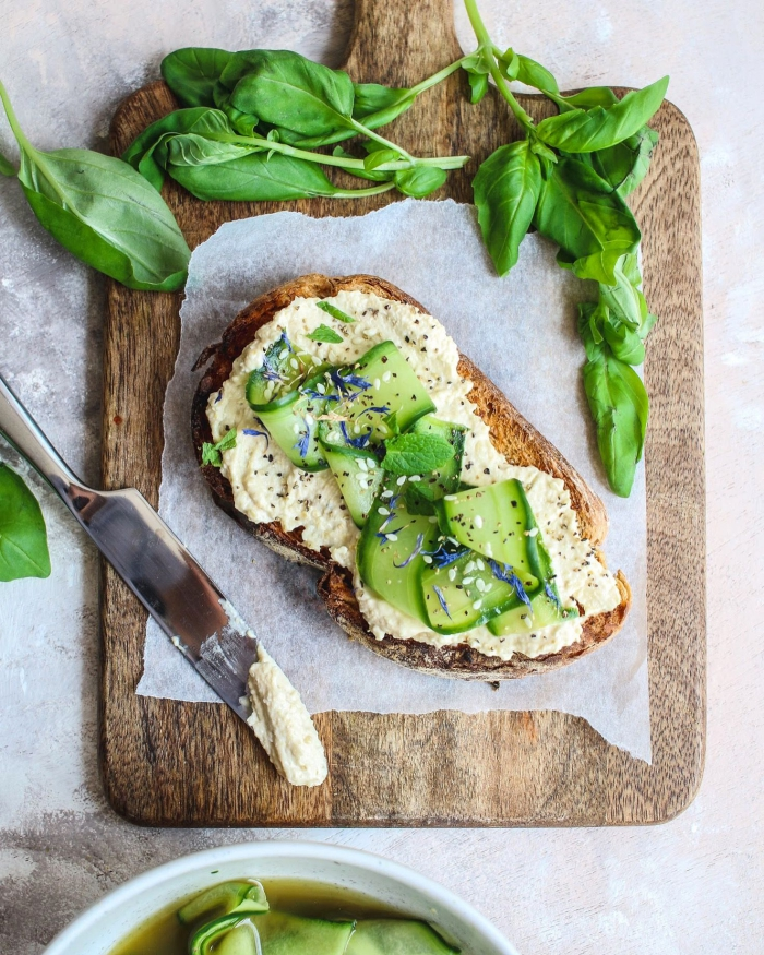vegan hummus toast with cucumber and leafy greens spinach
