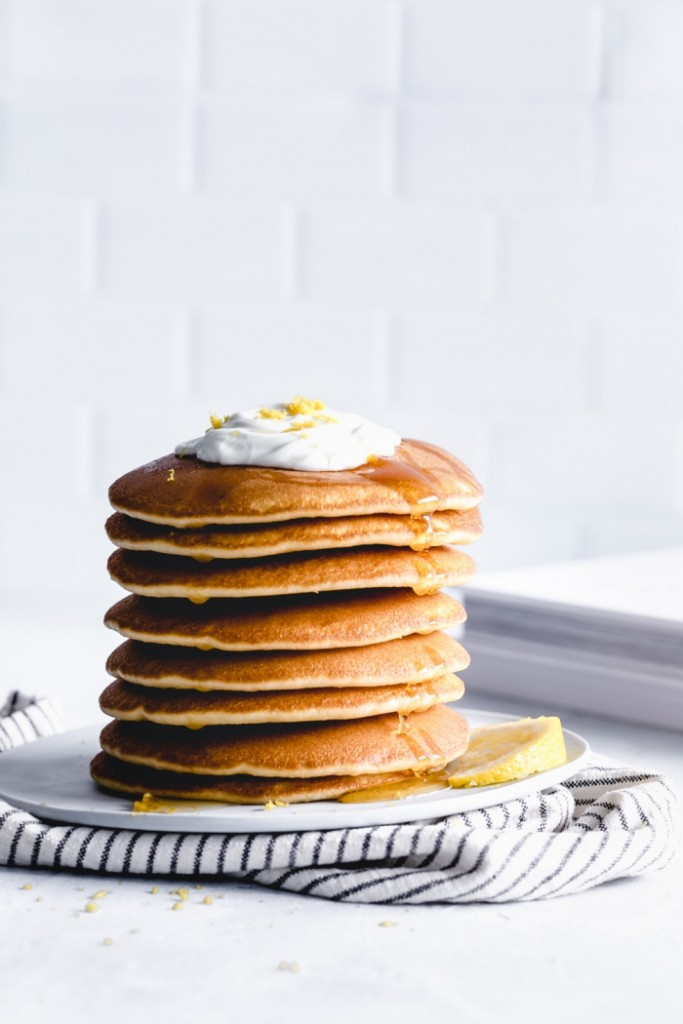 vegan breakfast stack of pancakes with cream and maple syrup