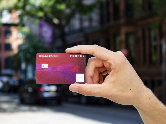 Hand holding Wells Fargo Propel American Express card city street background