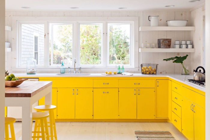 bright yellow and white kitchen with large windows