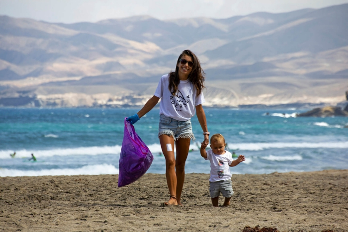 woman and baby walking on the beach cleaning with purple trash bag