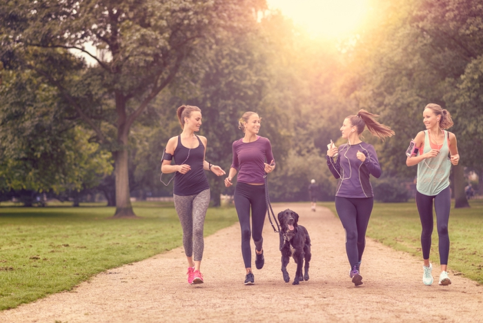 Four Healthy Young Women Jogging at the Park in the Afternoon with a dog
