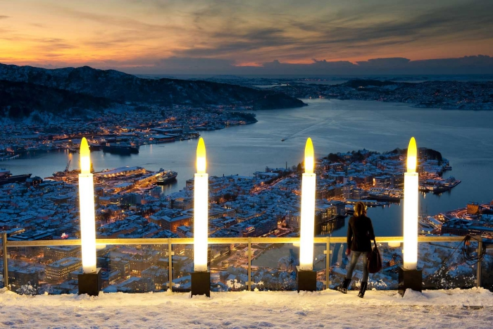 Woman standing on a decorated terrace overlooking Bergen in the evening
