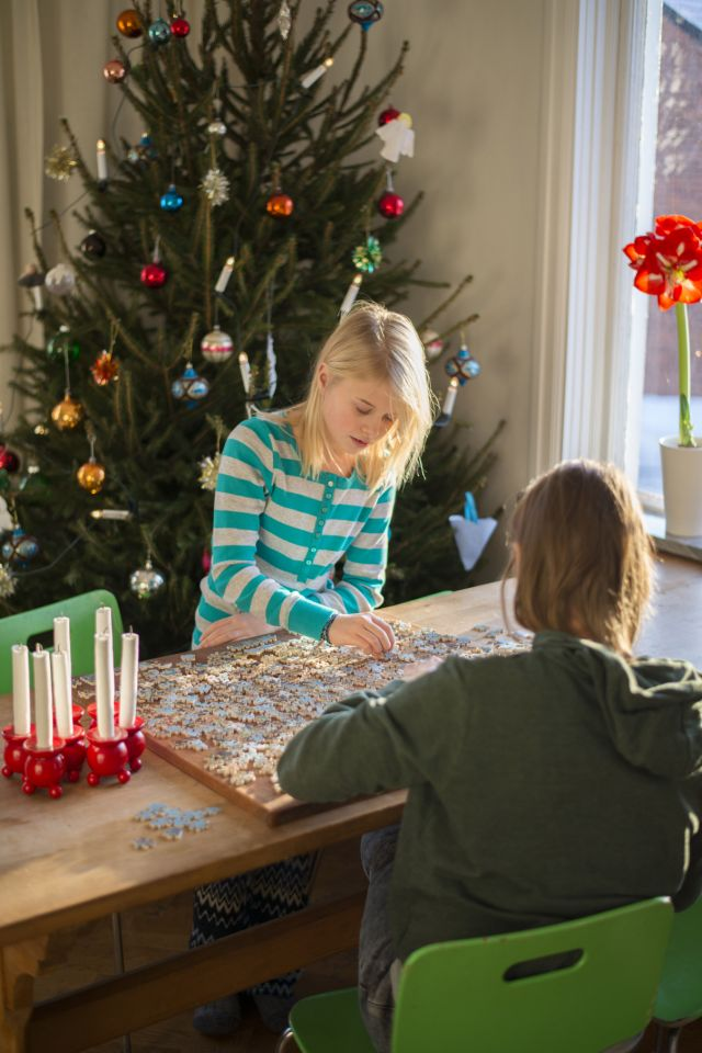 two girls playing board games at home Christmas tree in the background