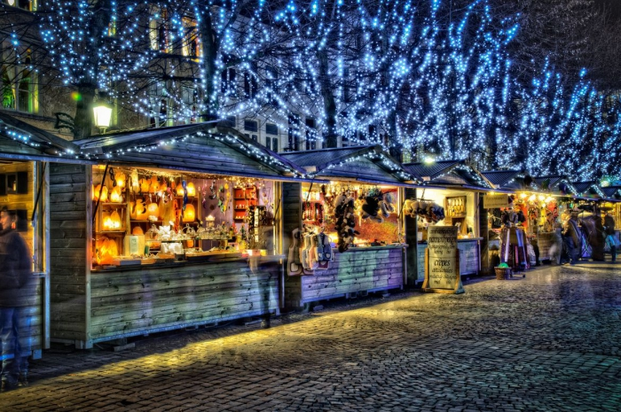 Bruges Christmas Market wooden pavilions with Christmas items and trees decorated with blue lights