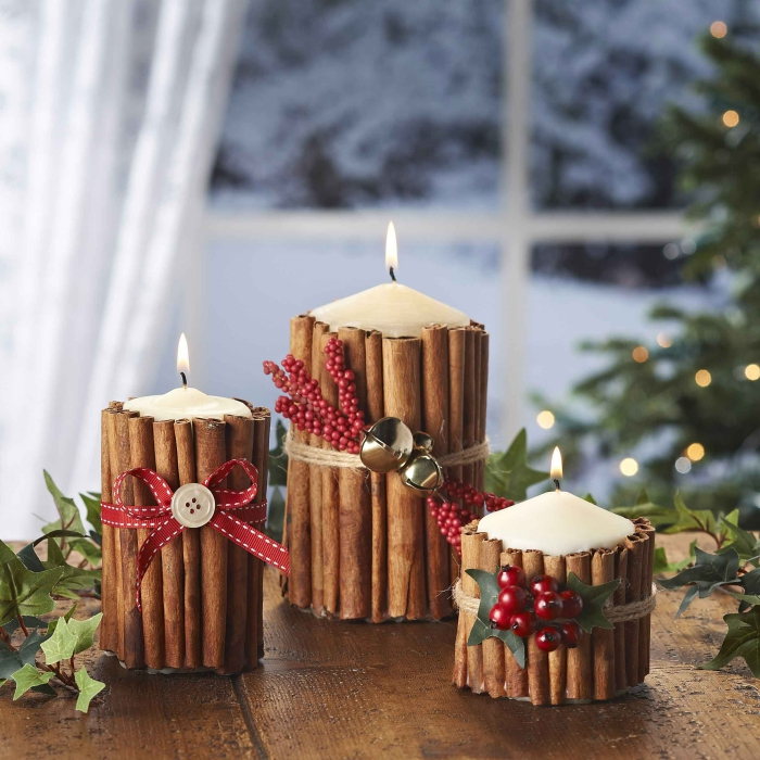Christmas Decorative Candles with cinnamon sticks and berries window in the background