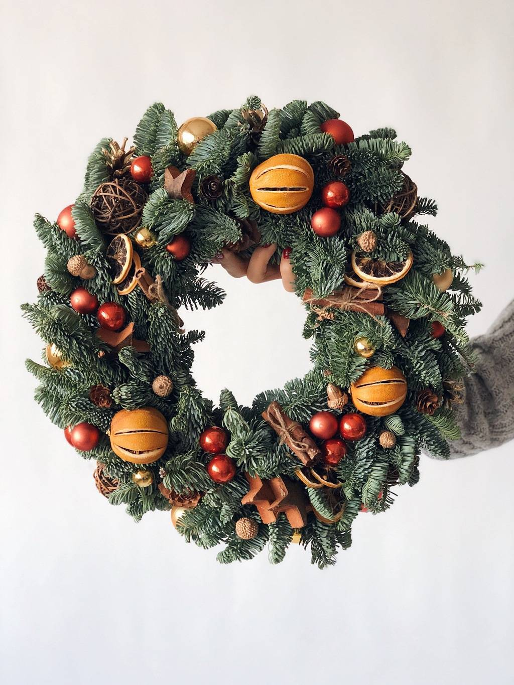 white background woman holding christmas wreath decorated with dried fruits