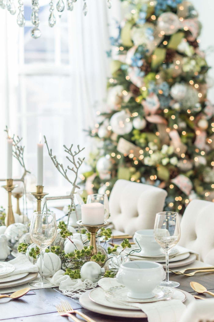 table decorated with natural christmas decorations in white golden and green christmas tree in the background