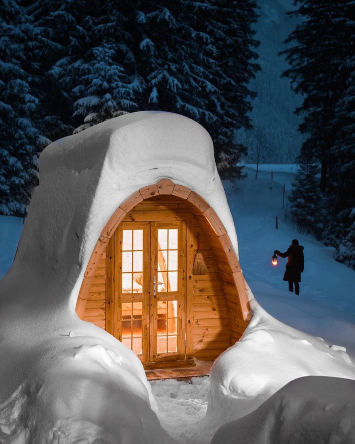 Christmas getaway in the woods cabin covered in snow woman with a lantern walking in background