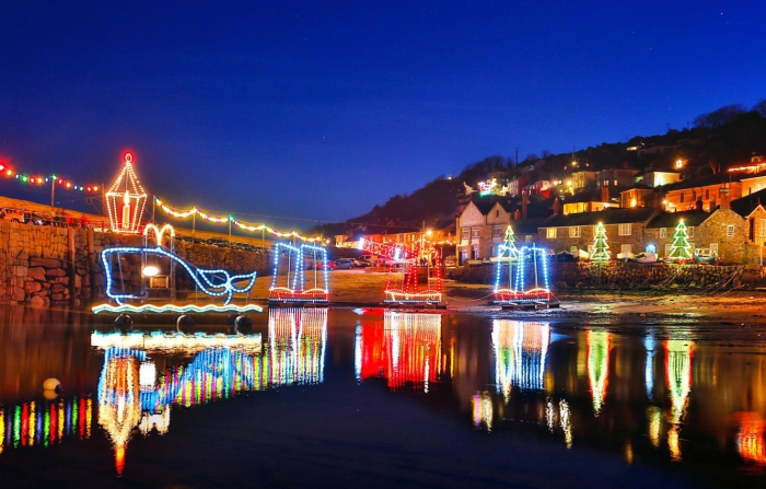 Halfpenny Christmas getaway ideas Cornwall lake with floating light decorations town in the background