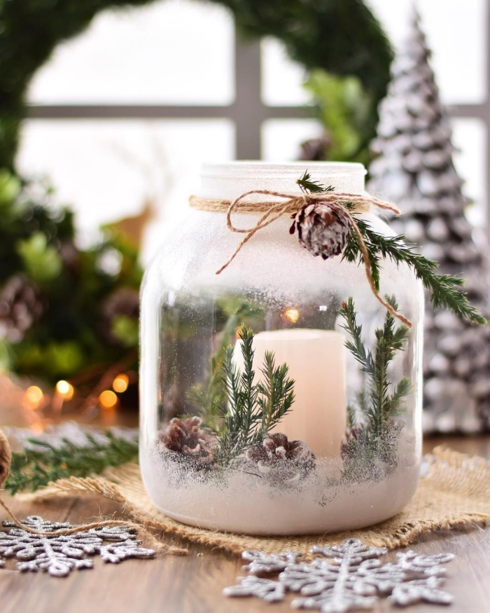 Spray painted glass jar with a candle pinecones and green branches