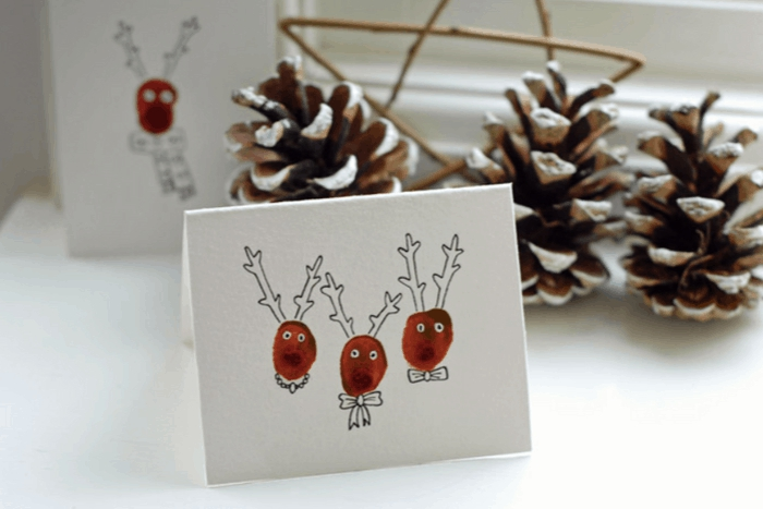Fingerprint Reindeer DIY Christmas cards ideas white card with three reindeer pinecones in the background