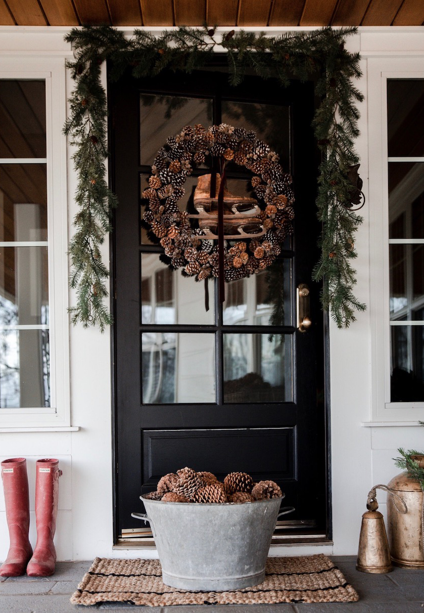 dark front door decorated with green branches and pinecone wreath pinecones in a bucket