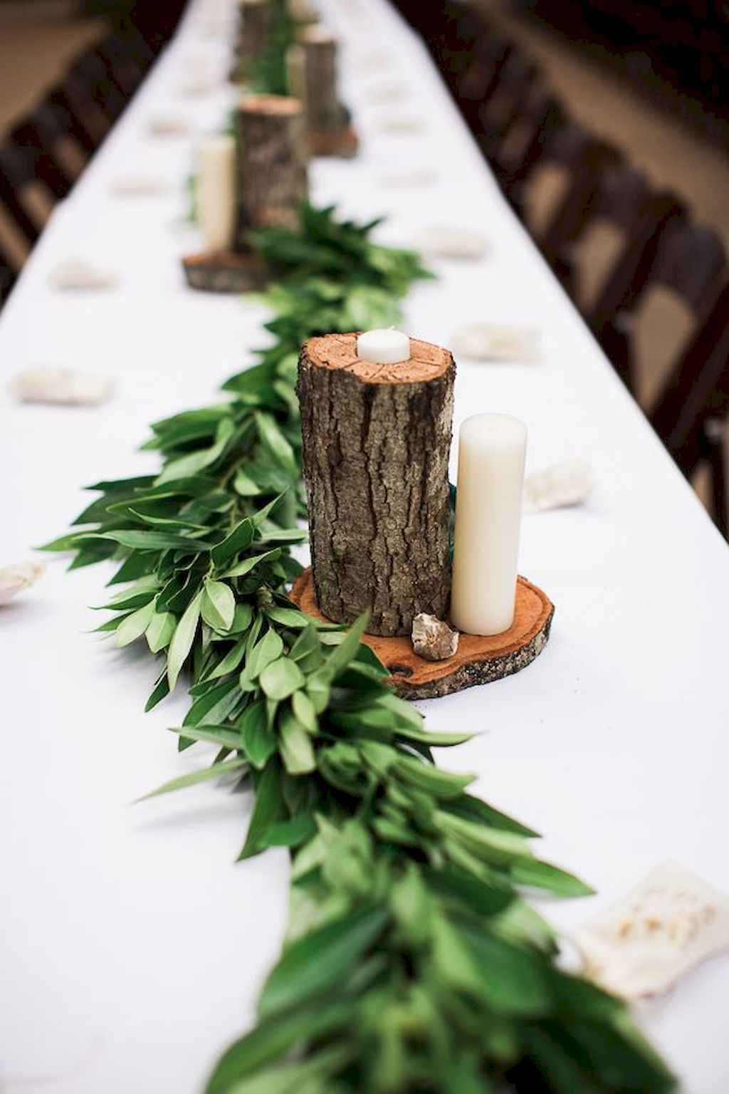 Green table centerpiece long table with tree log candle holders and branches white table cloth
