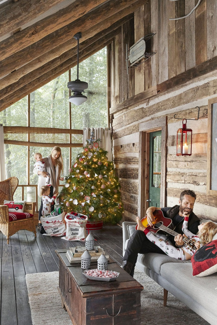 Cabin interior christmas tree family of four man with a guitar