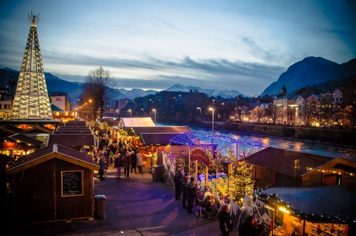 Innsbruck Christmas bazaar at night river view mountain tops large christmas outdoor tree
