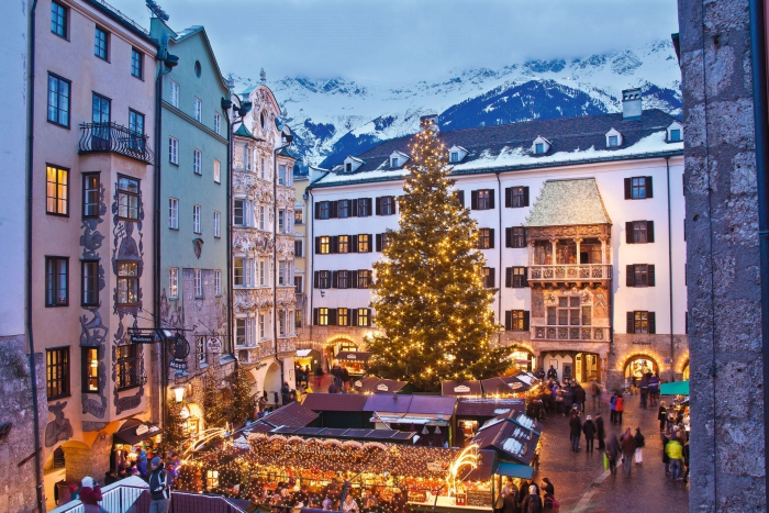 Innsbruck Christmas Market town square with a large christmas tree and mountain view behind the buildings