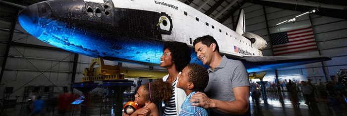 Family with kids in a museum looking at a plane