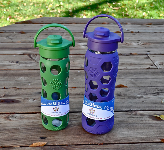 two water bottles with green and purple silicone sleeve outdoor
