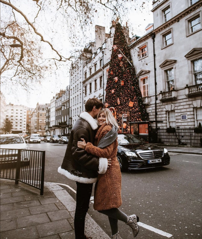 Couple hugging in front of large christmas tree in london
