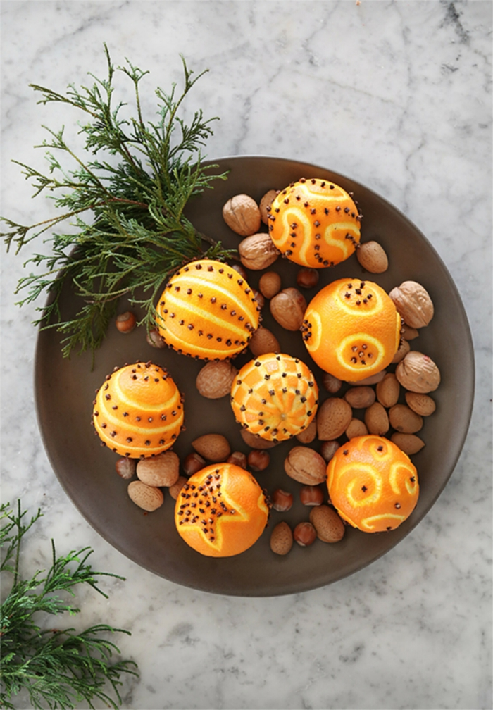 Christmas trends natural decor oranges cloves almonds green branch in a plate