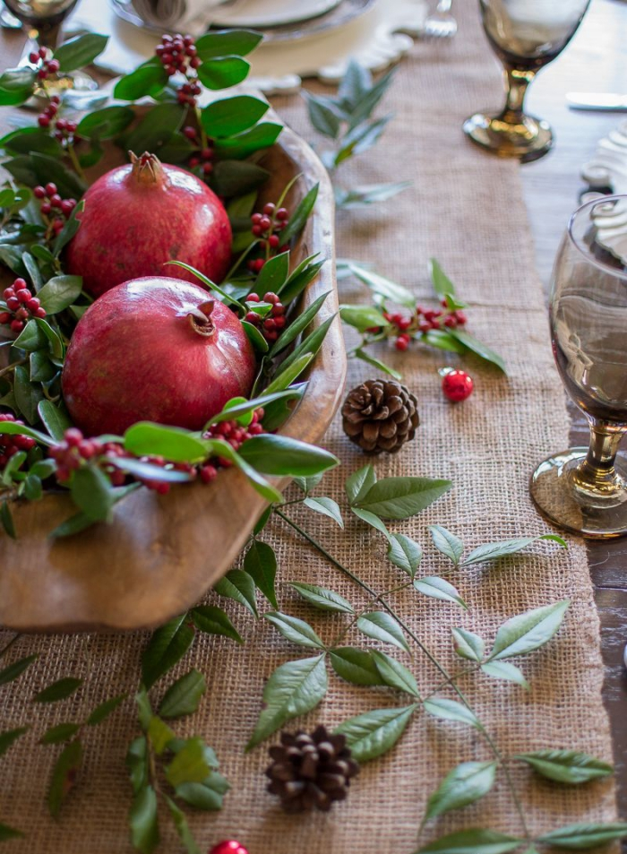 Natural table decor for Christmas centerpiece pomegranate berries green leaves