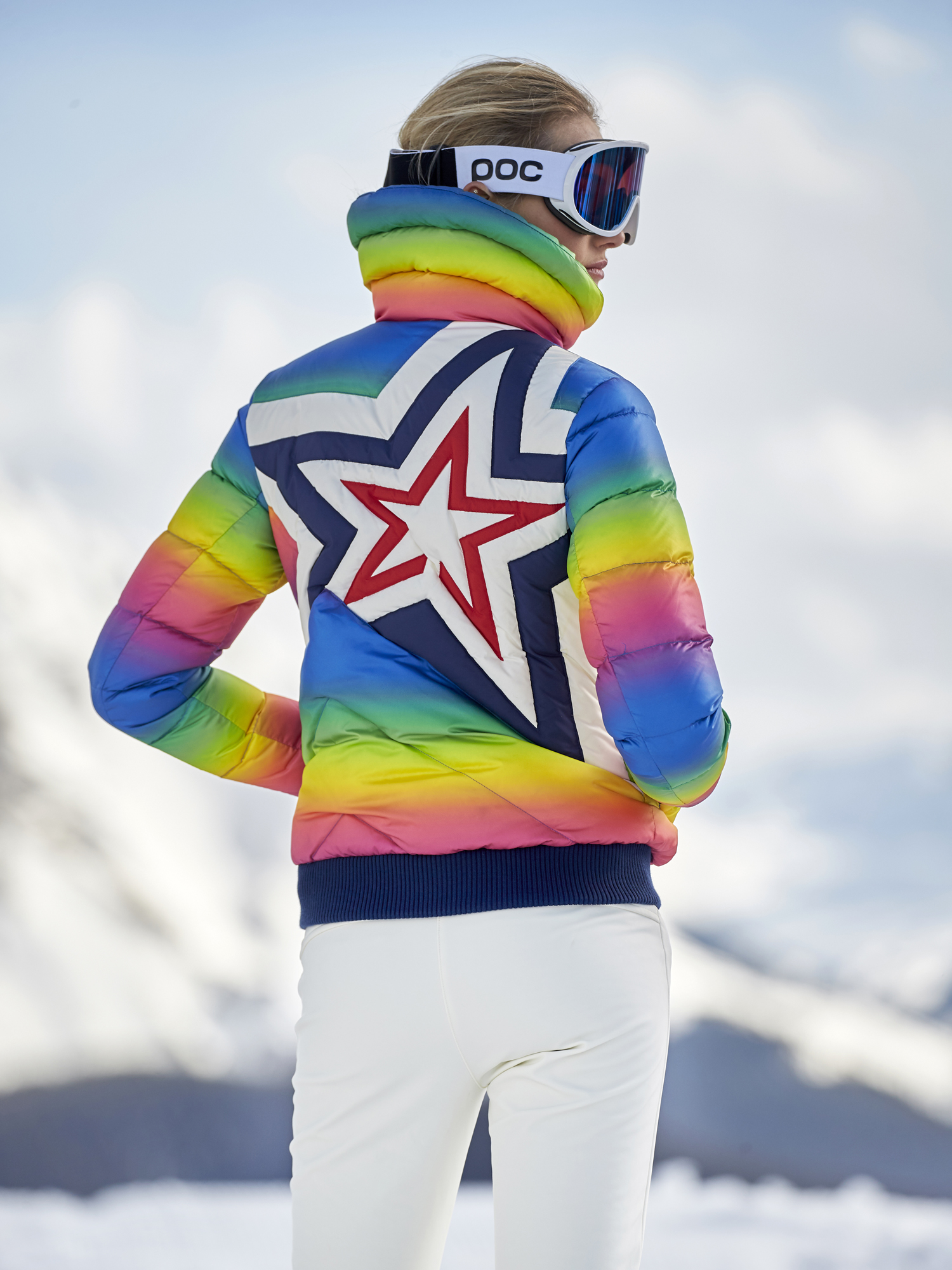 Neon ski wear trends woman in white pants and colorful neon jacket large futuristic ski glasses