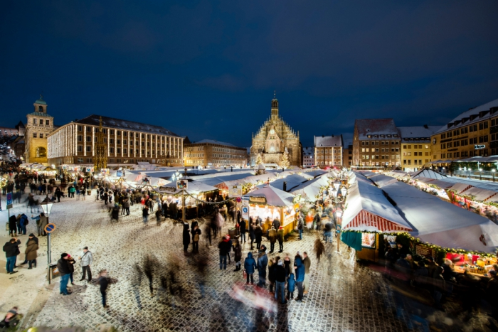 Nuremberg central square cathedral christmas bazaar stands people at night