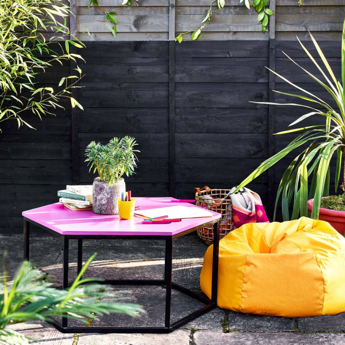 Patio area with bright statement furniture pink side table and bright yellow puff