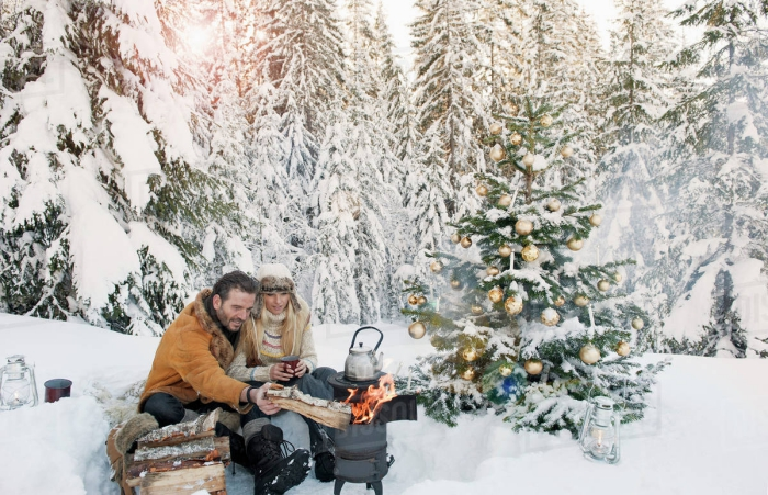 Couple in snowy forest campfire making tea decorated christmas tree
